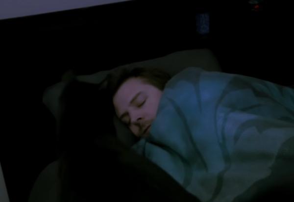 ベッドで寝ている人と猫