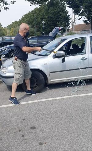 斧で車の窓ガラスを割る男性
